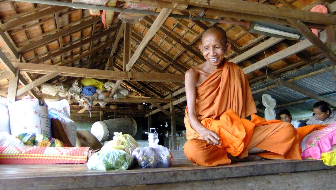Venerable May Sokhan at Wat Pratheath, smiling at the numerous dogs that live at the pagoda with the monks. (Photo by Rothany Srun)